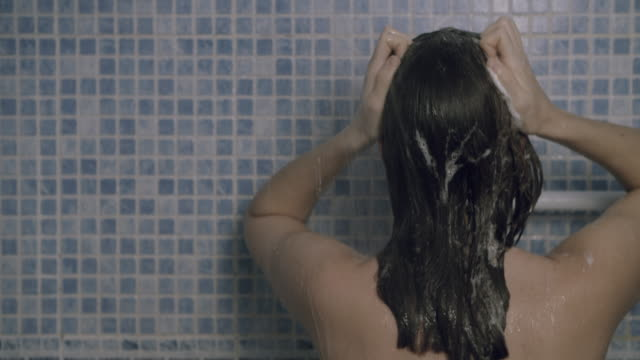 young woman washing her hair - washing hair stock videos & royalty-free footage