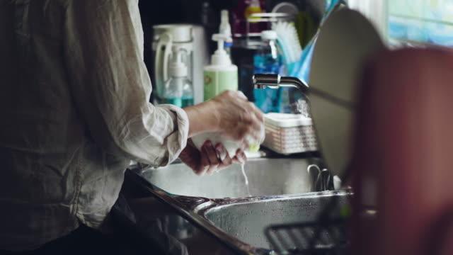 Junge Frau, die das Geschirr in der Spüle zu Hause