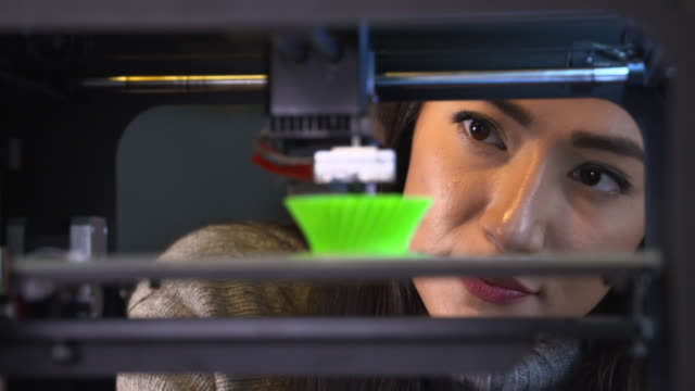 4k: young woman watching a 3d printer - 3d printing stock videos & royalty-free footage