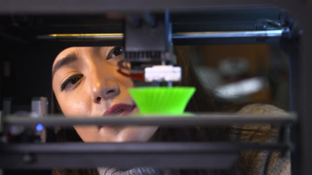4k: young woman watching a 3d printer - 3d printing stock videos and b-roll footage
