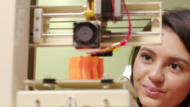 vídeos de stock, filmes e b-roll de jovem mulher assistindo uma impressora 3d - digitalização 3d