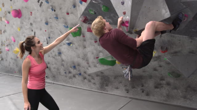 ms young woman watching a man climb a rock wall - climbing wall stock videos & royalty-free footage