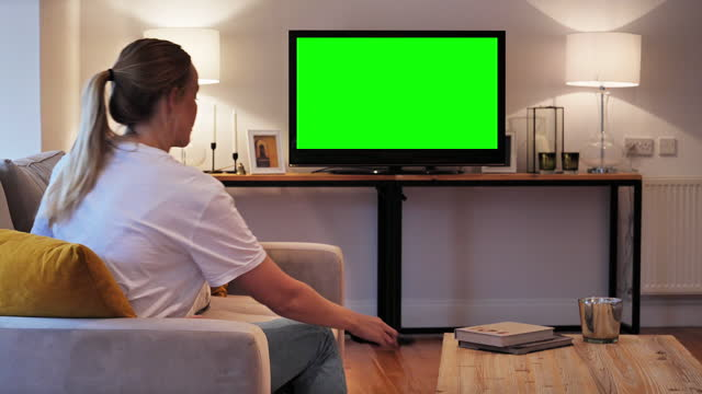 young woman watching chroma key tv- using remote control - television industry stock videos & royalty-free footage