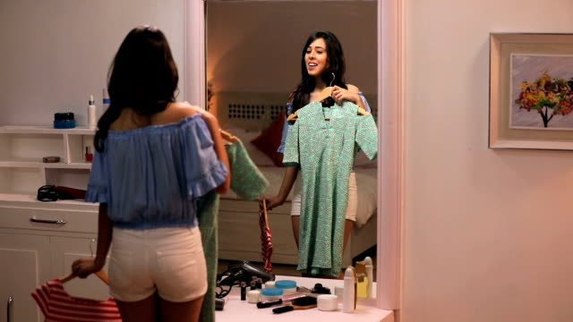 Young woman watching her dresses in the mirror, Delhi, India