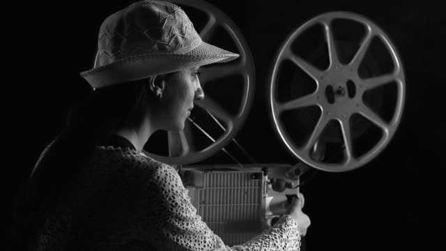 young woman watching movie in old fashioned style film projector - film director stock videos & royalty-free footage