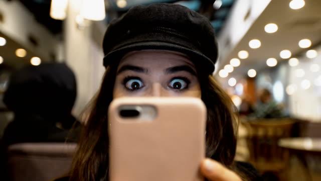 vídeos de stock, filmes e b-roll de jovem mulher assistindo no smartphone em estado de choque - shock
