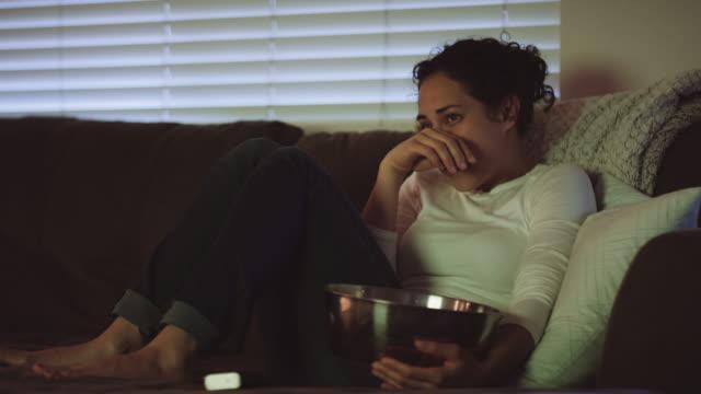 stockvideo's en b-roll-footage met jonge vrouw iets verontrustend op televisie kijken - fatcamera
