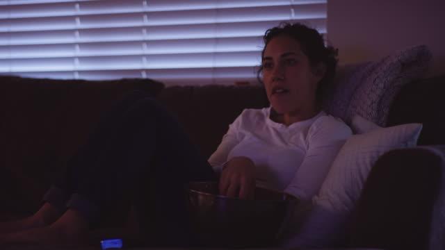 stockvideo's en b-roll-footage met jonge vrouw kijken iets op televisie die haar schokken - fatcamera