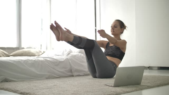 young woman watching tutorial lesson on laptop and doing yoga exercise at home - tutorial stock videos and b-roll footage