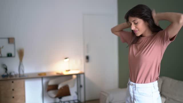 vidéos et rushes de jeune femme regardant la télévision et dansant à la maison - bien être