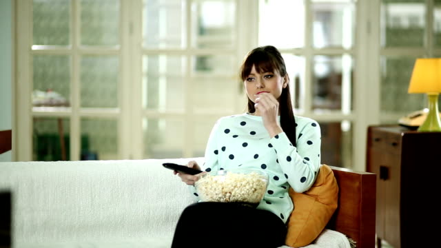 young woman watching tv and eating popcorn - cosy stock videos & royalty-free footage