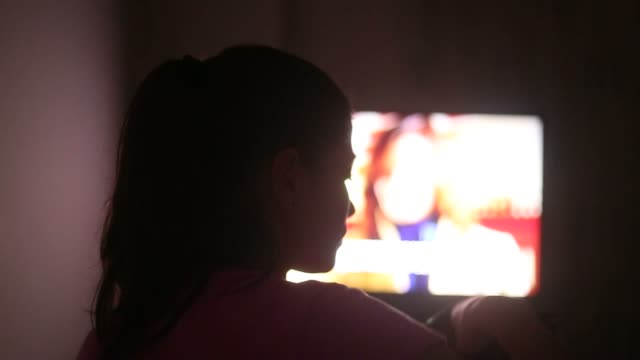 young woman watching tv late in night. - rear view stock videos & royalty-free footage