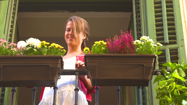 Young woman watering pots in balcony and smiling
