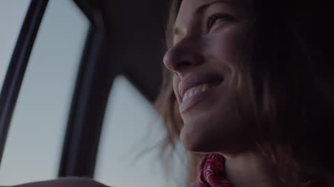 cu. young woman waves hand out car window and smiles on desert road trip. - le bildbanksvideor och videomaterial från bakom kulisserna