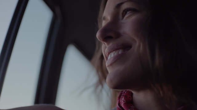 CU. Young woman waves hand out car window and smiles on desert road trip.