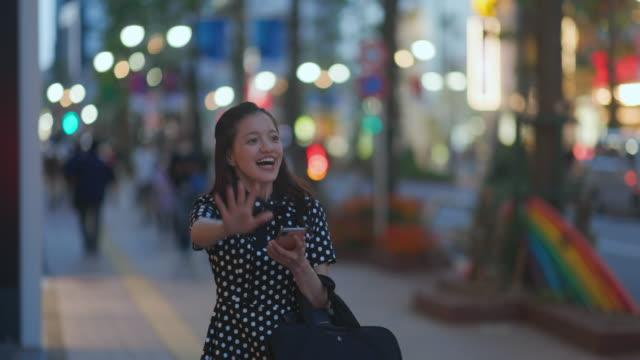 夜に街で手を振る若い女性, 彼女のボーイフレンドを見て - 待つ点の映像素材/bロール
