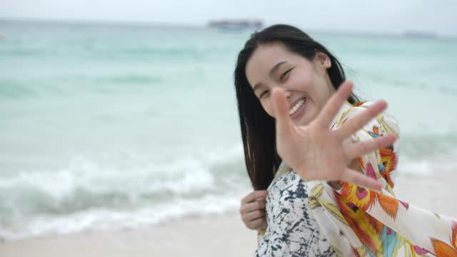 stockvideo's en b-roll-footage met jonge vrouw waving hand op het strand - lengte