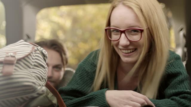 Jonge vrouw zwaaien, duimen opdagen en lachend op achterkant van de auto