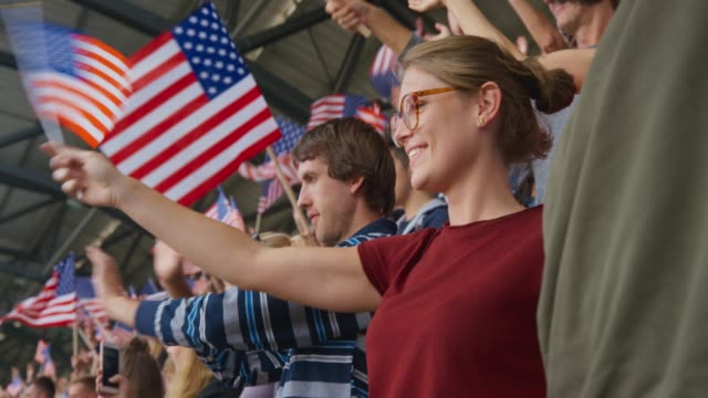 young woman waving the american flag on the crowded tribune - arms raised stock videos & royalty-free footage