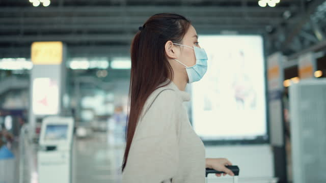 young woman wear surgical mask came to the airport early to prepare for the trip. - reportage stock videos & royalty-free footage