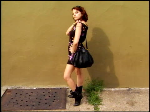 stockvideo's en b-roll-footage met young woman wearing a black floral romper with boots and large purse - haaraccessoires