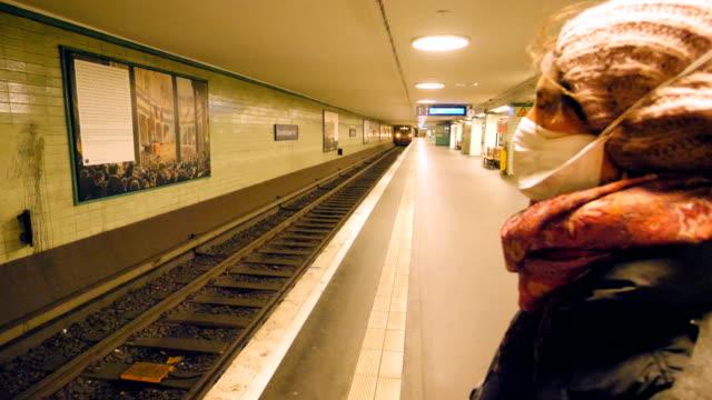 stockvideo's en b-roll-footage met jonge vrouw die een masker draagt dat in een leeg metrostation wacht - metro passagierstrein