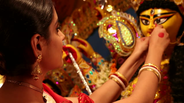 CU Young woman wearing a nose ring to Durga statue during Durga Puja festival / New Delhi, Delhi, India