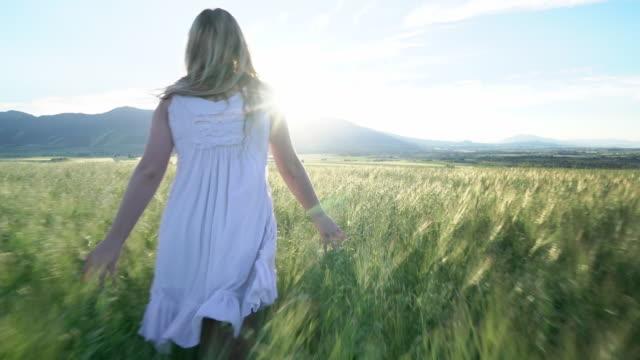 vídeos de stock e filmes b-roll de ws sm young woman wearing a white dress, walking in a wheatfield - vestido branco