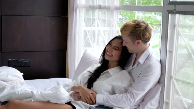 young woman wearing a white shirt laying in the lap for a foreign boyfriend on a bed in the morning. - white shirt stock videos & royalty-free footage