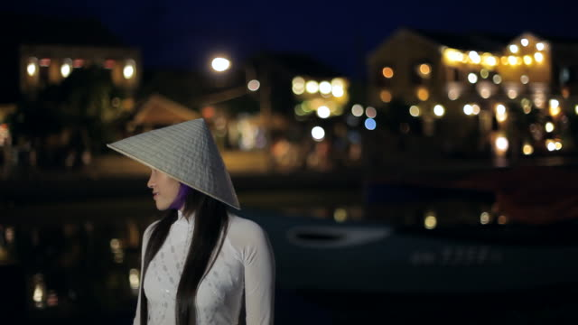 mh ld young woman wearing ao dai and straw hat at night / hoi an, vietnam - straw hat stock videos & royalty-free footage