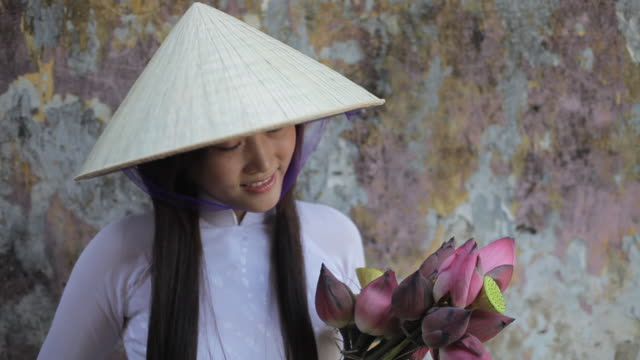 mh ld young woman wearing ao dai and straw hat holding flowers / hoi an, vietnam - straw hat stock videos & royalty-free footage
