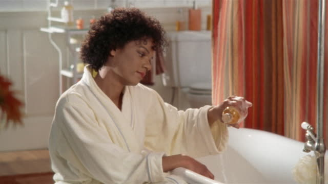 ms, pan, young woman wearing bathrobe pouring bath oil into bathtub - bubble bath stock videos and b-roll footage