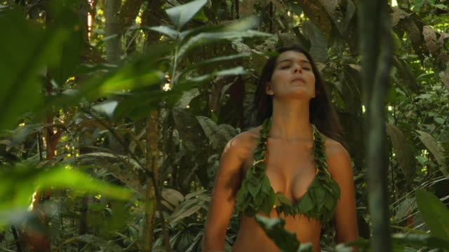 MS, Young woman wearing bikini made of leaves standing in jungle, Manaus, Brazil