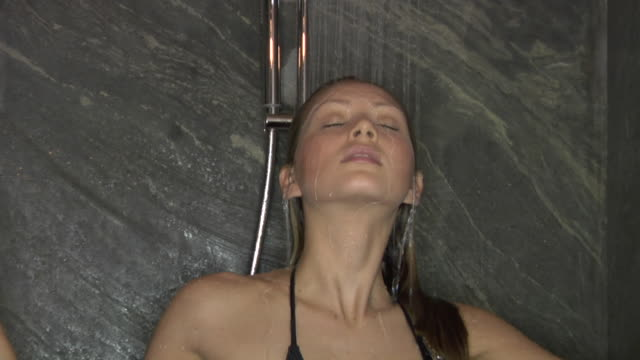 zi, cu, young woman wearing bikini taking shower - dusche stock-videos und b-roll-filmmaterial