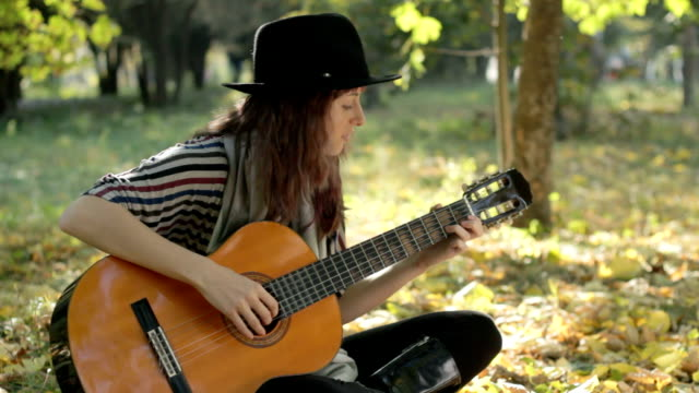 Young woman wearing black hat, playing guitar in park, summer.