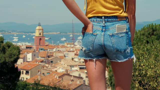 young woman wearing denim shorts, st tropez old town in the background - celebrity sightings stock videos & royalty-free footage