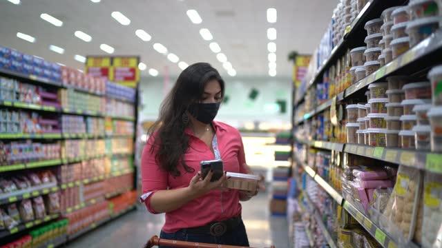 junge frau trägt gesichtsmaske untersuchung produkte in supermarkt gang - 4k auflösung stock-videos und b-roll-filmmaterial