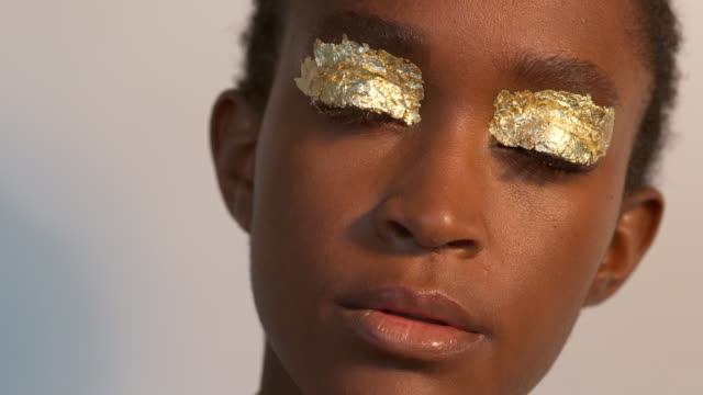 a young woman wearing gold leaf above her eyes. - gold leaf stock videos & royalty-free footage