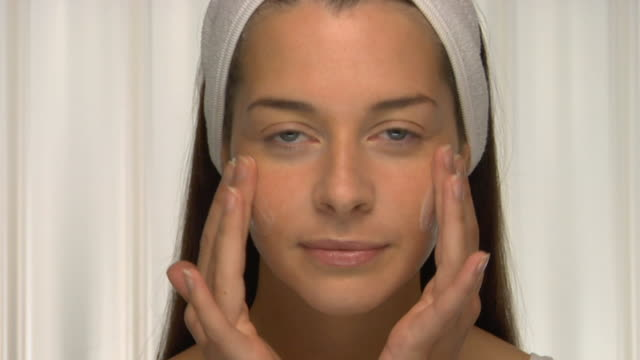cu, young woman wearing head band applying cream on face, portrait - face cream stock videos and b-roll footage