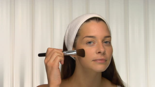 cu, young woman wearing head band applying powder on face, portrait - self improvement stock videos & royalty-free footage