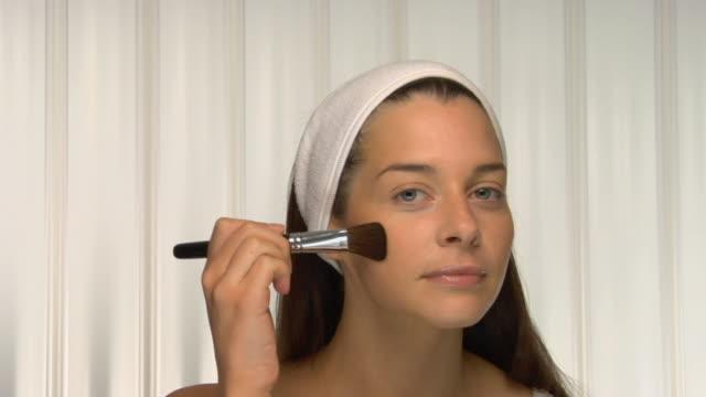 vídeos y material grabado en eventos de stock de cu, young woman wearing head band applying powder on face, portrait - cabello recogido
