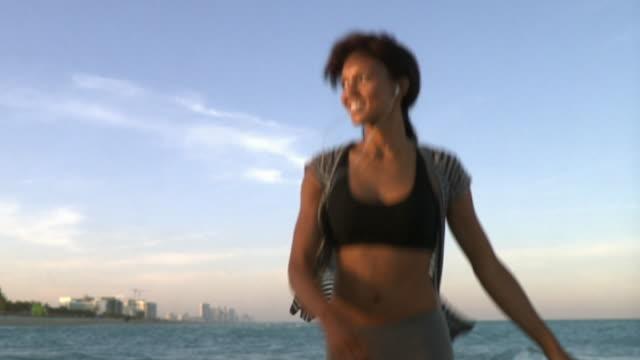 vídeos y material grabado en eventos de stock de slo mo ms young woman wearing headphones dancing on beach, south beach, florida, usa - miami