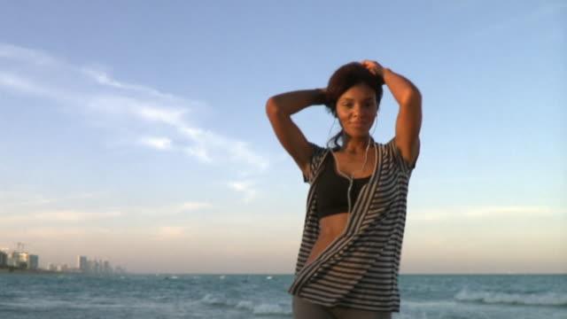 SLO MO MS Young woman wearing headphones dancing on beach, South Beach, Florida, USA
