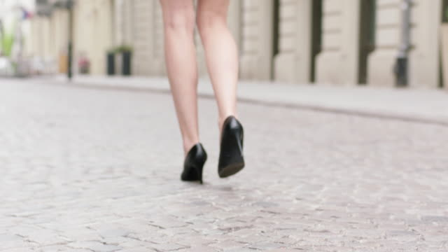 街を歩いてかかとを身に着けている若い女性。足のクローズ アップ - 人の脚点の映像素材/bロール