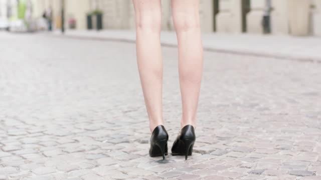 vídeos y material grabado en eventos de stock de joven mujer llevando tacones caminando por la ciudad. de cerca en las piernas - espalda partes del cuerpo