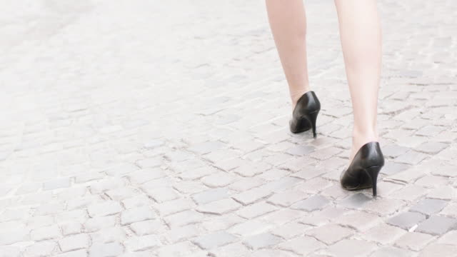 Young woman wearing heels walking in the city. Close up on legs