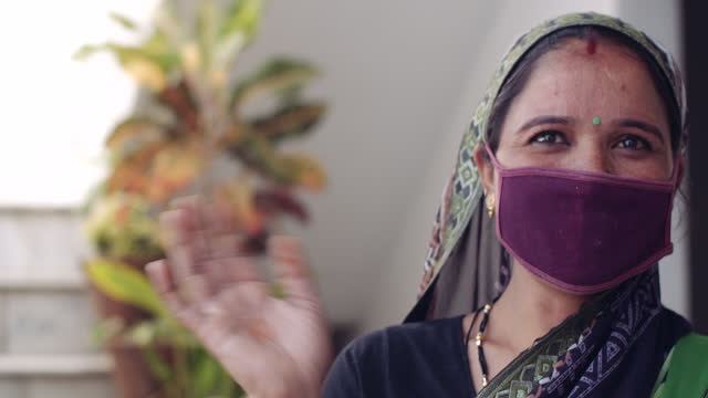 young woman wearing mask at home and looking at camera as she waves goodbye and exists leaves the frame - traditional clothing stock videos & royalty-free footage