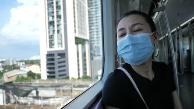 junge frau trägt maske in elektrischen zügen - bahnreisender stock-videos und b-roll-filmmaterial