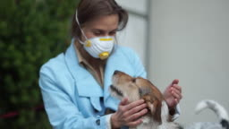 Young woman wearing medical face mask sitting together with her dog. Coronavirus concept, covid-19