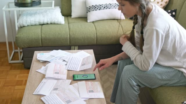 vídeos de stock e filmes b-roll de young woman wearing pajamas, stressing over bills early in the morning - braided hair